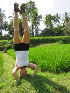 Kajta doing head stand in the rice field