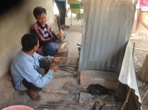 Mr. Pahn and Ahn (my guide) looking at a Laotian knife and the raw metal we just wedged of the car spring.